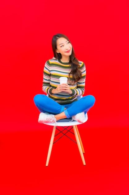빨간색 격리 된 벽에 커피 컵 초상화 아름 다운 젊은 아시아 여자 무료 사진