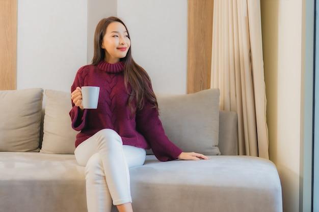 肖像画のリビングルームのソファ装飾インテリアにコーヒーカップを持つ美しい若いアジア女性 無料写真