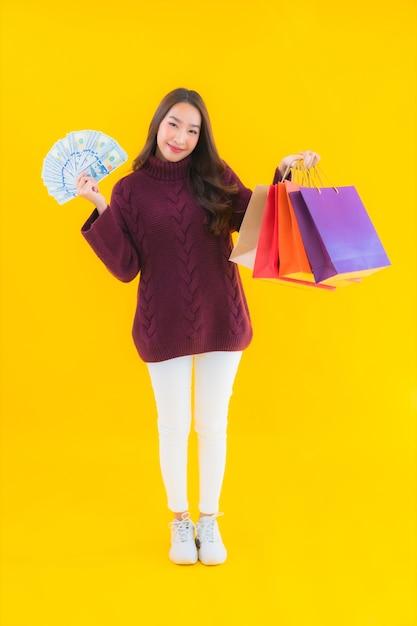 カラフルな買い物袋を持つ肖像画の美しい若いアジアの女性 無料写真