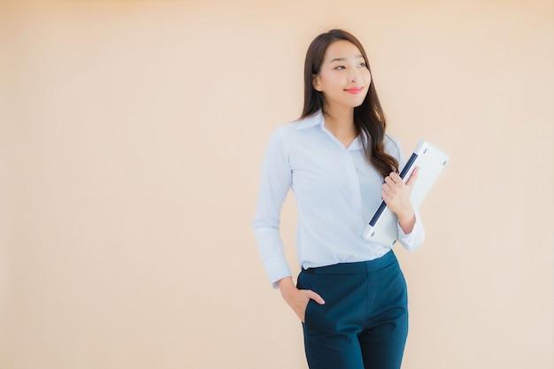 Женщина портрета красивая молодая азиатская с компьтер-книжкой компьютера для работы Бесплатные Фотографии