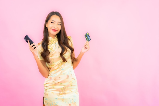 신용 카드와 핑크 색상 벽에 휴대 전화 초상화 아름 다운 젊은 아시아 여자 무료 사진