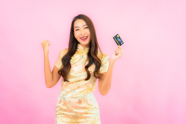 Женщина портрета красивая молодая азиатская с кредитной картой и мобильным телефоном на стене розового цвета Бесплатные Фотографии