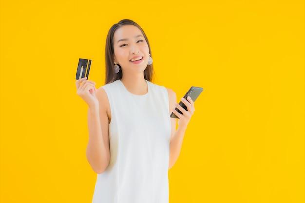 オンラインショッピングのためのクレジットカードを持つ美しい若いアジア女性の肖像画 無料写真