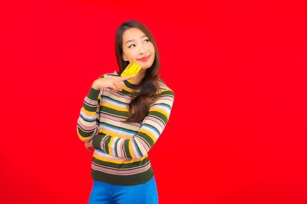 赤い孤立した壁にクレジットカードを持つ肖像画美しい若いアジアの女性 無料写真