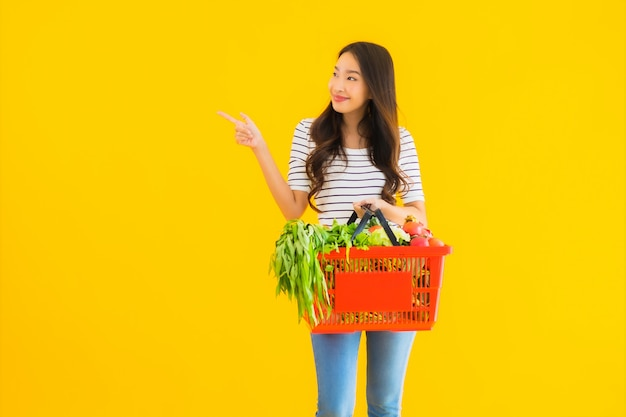 Portrait beautiful young asian woman with grocery basket cart from supermarket in shopping mall Free Photo