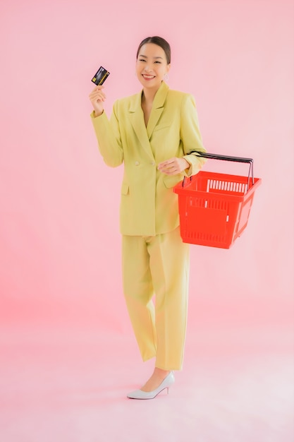 Portrait beautiful young asian woman with grocery basket from supermarket on color Free Photo