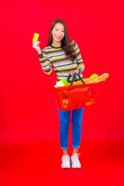 빨간색 격리 된 벽에 슈퍼마켓에서 식료품 바구니와 세로 아름 다운 젊은 아시아 여자 무료 사진