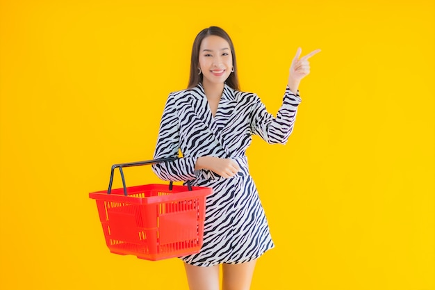 Portrait beautiful young asian woman with grocery basket for shopping on yellow Free Photo