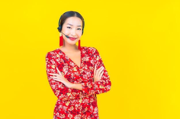 Женщина портрета красивая молодая азиатская с наушниками для заботы центра телефонного обслуживания клиента на желтой стене Бесплатные Фотографии