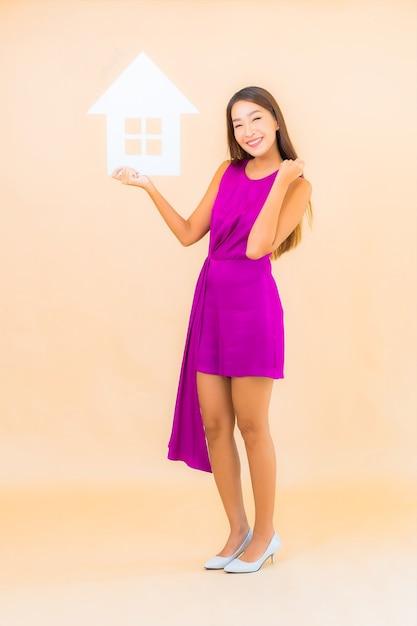 Женщина портрета красивая молодая азиатская с домашней вывеской на фоне изолированной цветом Бесплатные Фотографии