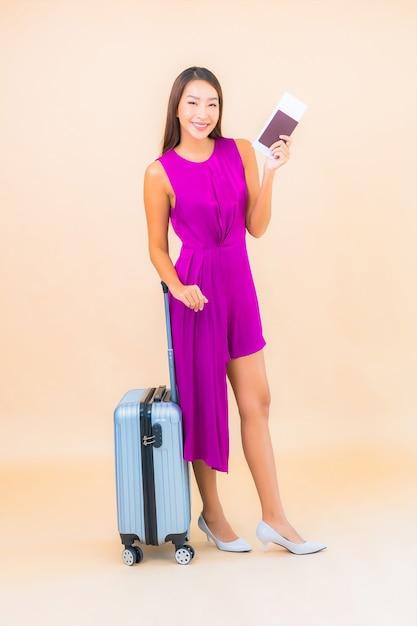 Ritratto bella giovane donna asiatica con bagagli e biglietto aereo su sfondo colorato Foto Gratuite