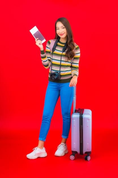 Женщина портрета красивая молодая азиатская с багажом и посадочным талоном на красной стене Бесплатные Фотографии