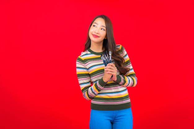赤い壁に化粧ブラシと化粧品で美しい若いアジアの女性の肖像画 無料写真