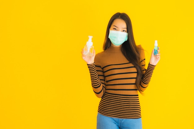 Portrait beautiful young asian woman with mask alcohol spray and gel bottle in her hand for protect from coronavirus or covid19 Free Photo