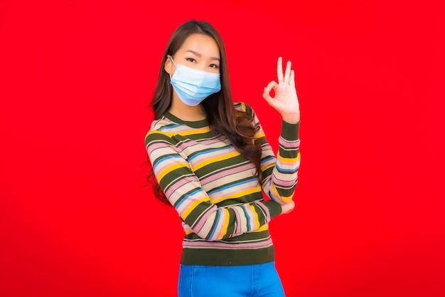 Портрет красивой молодой азиатской женщины с маской для защиты covid19 Бесплатные Фотографии
