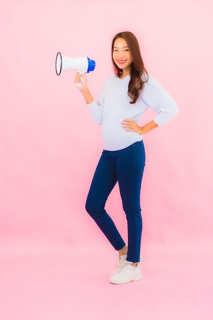 Женщина портрета красивая молодая азиатская с мегафоном для связи на розовой изолированной стене Бесплатные Фотографии