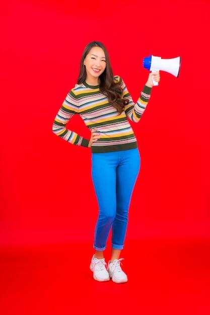 赤い壁の通信のためのメガホンと肖像画の美しい若いアジアの女性 無料写真