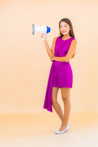 Женщина портрета красивая молодая азиатская с мегафоном на фоне изолированной цветом Бесплатные Фотографии