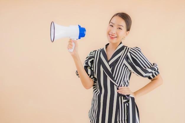 メガホンを持つ美しい若いアジア女性の肖像画 無料写真