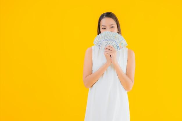 Ritratto bella giovane donna asiatica con denaro contante Foto Gratuite