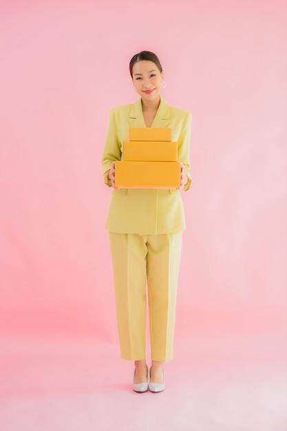 Ritratto bella giovane donna asiatica con cassetta dei pacchi sul colore Foto Gratuite