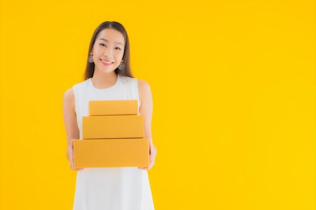 Ritratto bella giovane donna asiatica con cassetta dei pacchi Foto Gratuite