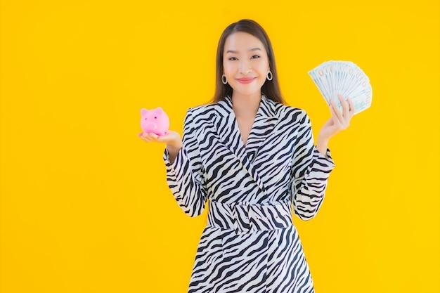 肖像画貯金箱と現金または黄色のお金を持つ美しい若いアジア女性 無料写真