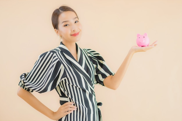 Portrait beautiful young asian woman with pink piggy bank Free Photo