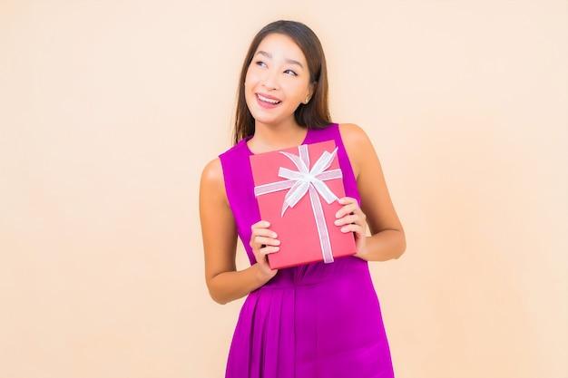 Женщина портрета красивая молодая азиатская с красной подарочной коробкой на фоне изолированной цветом Бесплатные Фотографии