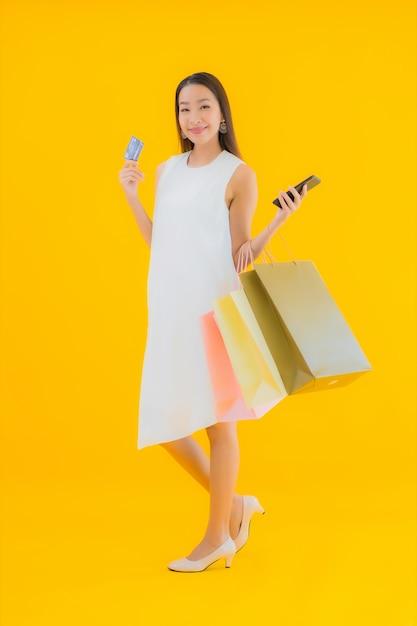 肖像画小売デパートからの買い物袋を持つ美しい若いアジア女性 無料写真