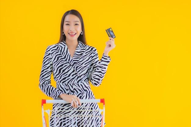 肖像画黄色の食料品の買い物のためのショッピングカートと美しい若いアジア女性 無料写真