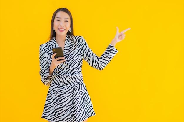 スマート携帯電話と黄色のクレジットカードの肖像若い美しいアジアの女性 無料写真
