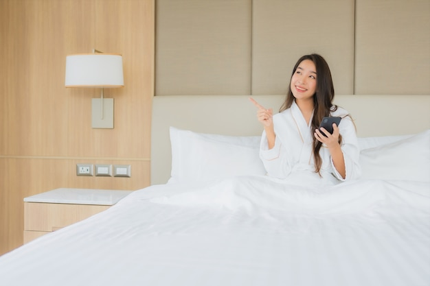 Portrait beautiful young asian woman with smart mobile phone in bedroom Free Photo