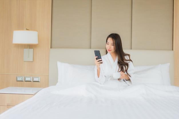 肖像画の寝室でスマートな携帯電話を持つ美しい若いアジア女性 無料写真