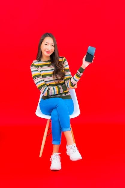 빨간색 격리 된 벽에 스마트 휴대 전화와 세로 아름 다운 젊은 아시아 여자 무료 사진