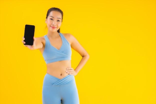肖像画分離された黄色のスマート携帯電話を持つ美しい若いアジア女性 無料写真