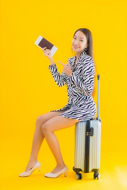 旅行の荷物のパスポートと搭乗券の黄色の美しい若いアジア女性の肖像画 無料写真