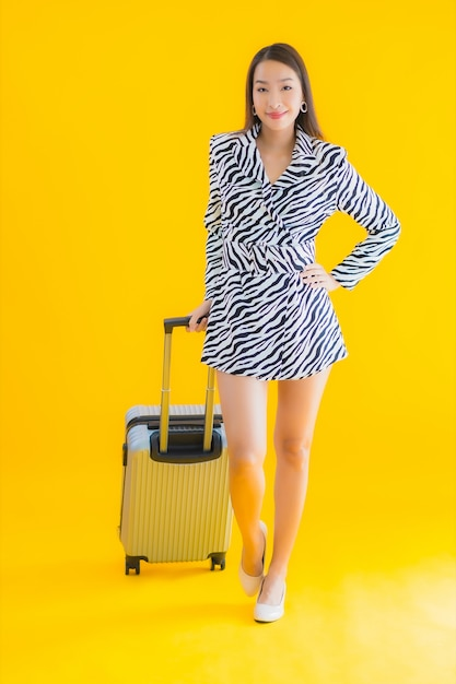 Portrait beautiful young asian woman with travel luggage passport and boarding pass on yellow Free Photo