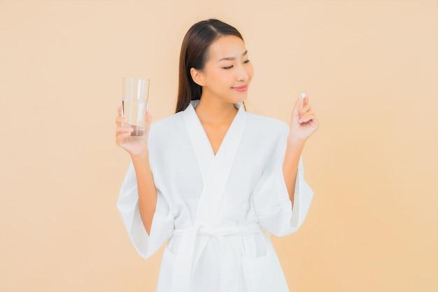 Женщина портрета красивая молодая азиатская с стеклом воды и пилюлькой лекарства на бежевом Бесплатные Фотографии