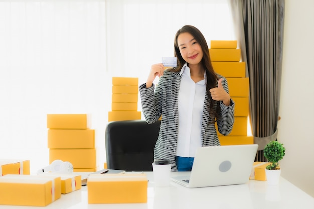 Portrait beautiful young asian woman work from home with credit card and cardboard box ready for shipping of shopping Free Photo