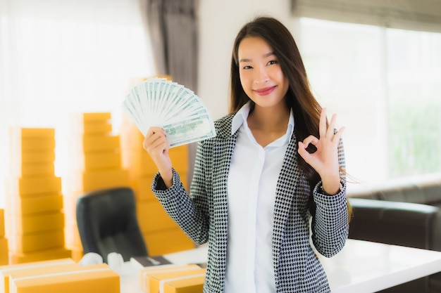 Portrait beautiful young asian woman work from home with laptop cash and cardboard box ready for shipping of online Free Photo