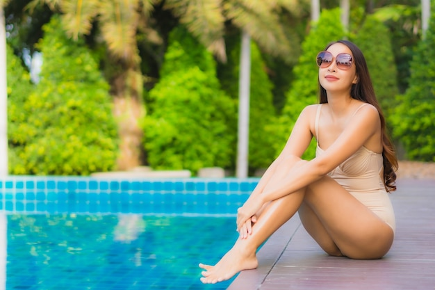 Portrait beautiful young asian women happy smile relax outdoor swimming pool in resort Free Photo