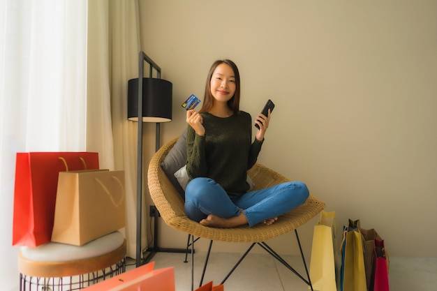 Portrait beautiful young asian women using mobile phone with credit card for online shopping Free Photo