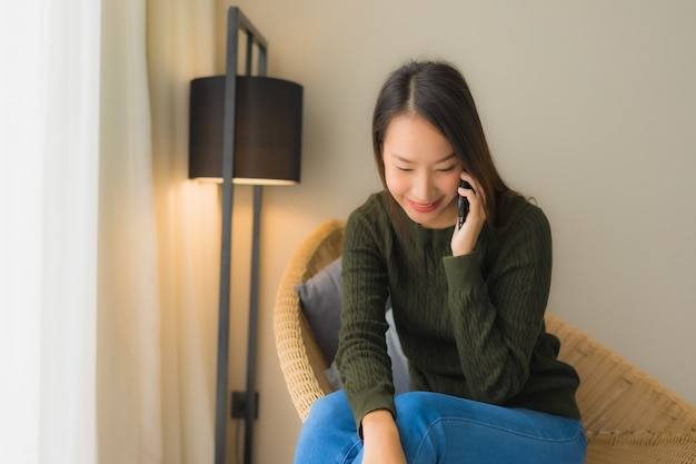 Portrait beautiful young asian women using talking mobile phone and sitting on sofa chair Free Photo