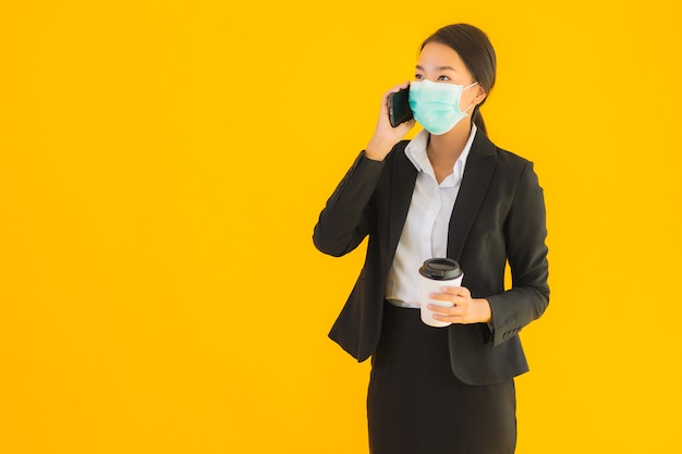 Portrait beautiful young business asian woman wear mask use mobile phone with coffee Free Photo