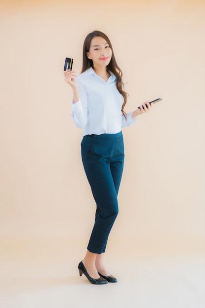Ritratto bella giovane donna asiatica di affari con il telefono e la carta di credito Foto Gratuite