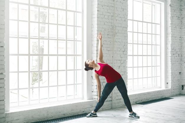 Ritratto di bella giovane femmina caucasica in abiti sportivi alla moda lavorando nella spaziosa sala luminosa da grandi finestre, facendo esercizio di piegatura laterale. yoga, fitness, sport e concetto di stile di vita sano Foto Gratuite