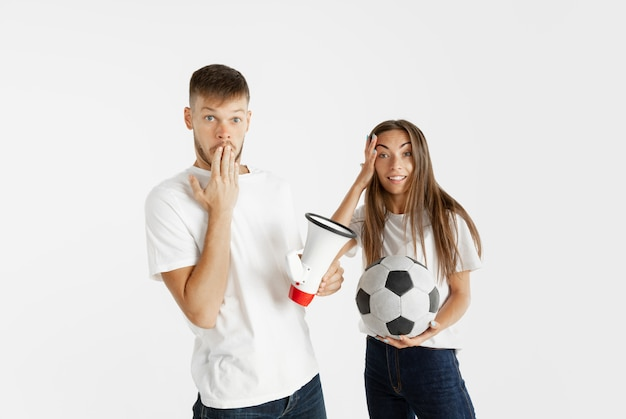 Portrait of beautiful young couple football or soccer fans on white wall. facial expression, human emotions, advertising, sport concept. woman and man jumping, screaming, having fun. Free Photo