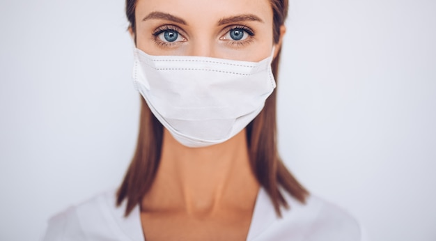 Portrait of beautiful young doctor wearing protective mask Premium Photo
