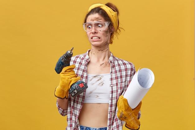 Ritratto di bella giovane donna che indossa camicia, top bianco e occhiali protettivi tenendo trapano e carta arrotolata guardando con sguardo disgustoso al trapano isolato sopra il muro giallo Foto Gratuite